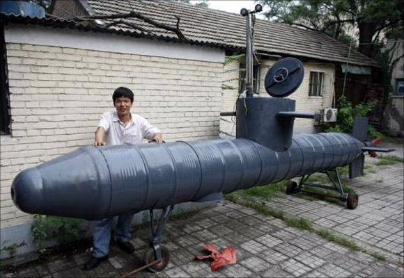 Tao Xiangli stands beside his homemade submarine in a courtyard in Beijing.