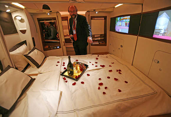 A journalist inspects a double bed in first-class suite.
