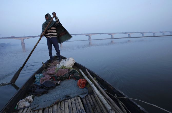 A man rows his boat in the waters of river Ganges with Mahatma Gandhi Setu bridge seen in the background in the eastern Indian city of Patna, in Bihar state.