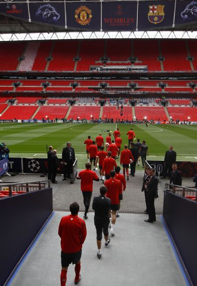 Manchester United players walk out onto the pitch for a training session at Wembley Stadium in London.