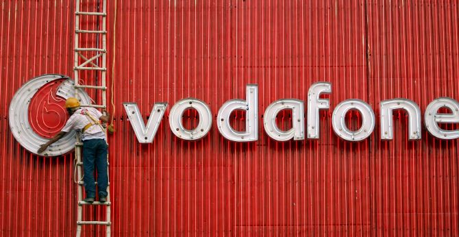 A worker replaces fluorescent lights on a Vodafone billboard in New Delhi.