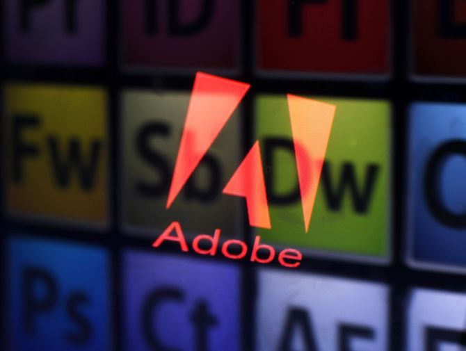 An Adobe logo and Adobe products are seen reflected on a monitor display.