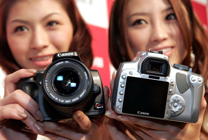 Models pose with Canon's EOS Kiss Digital X SLR camera, at the Canon headquarters in Tokyo.
