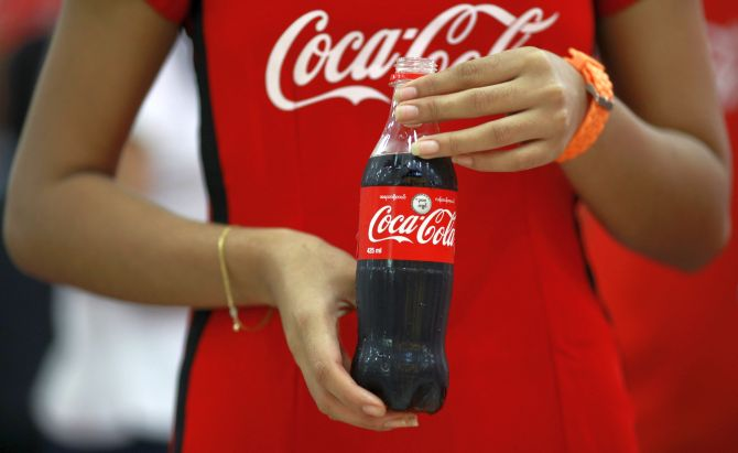 A promotion lady holds a new 425 ml Coca-Cola bottle during an event.