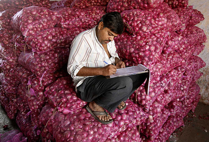 A trader works on his accounts while sitting on sacks of onions at a wholesale market in Ahmedabad.