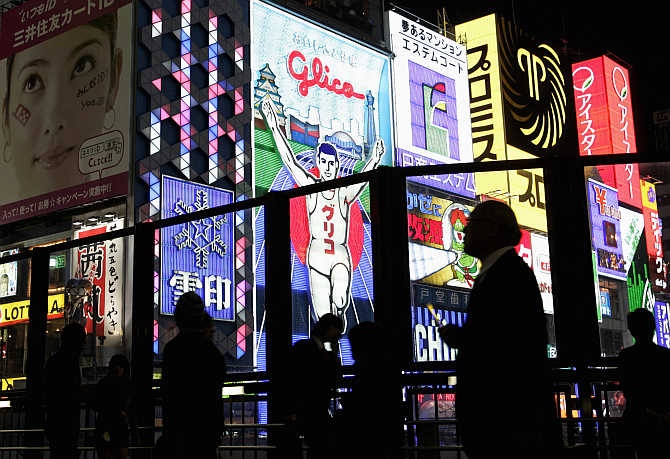 Passers-by are silhouetted against advertisements in the Dotonbori shopping and amusement district in Osaka.