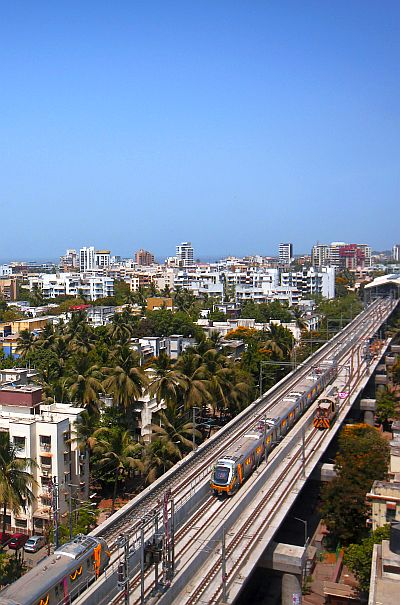 Metro trains pass through a residential area in Mumbai during its first official safety trial run.