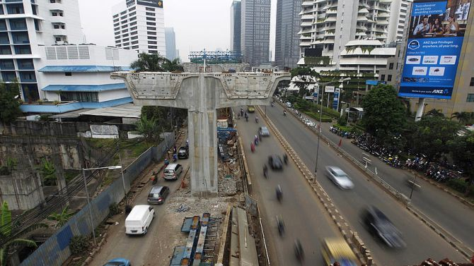 Vehicles drive past the construction site for a new highway in the business district in Jakarta.