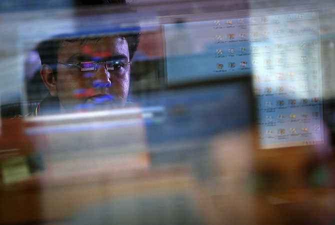 A broker monitors share prices while trading at a firm in Mumbai.