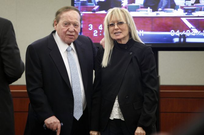 Las Vegas Sands Corp Chairman and Chief Executive Sheldon Adelson is accompanied by his wife Miriam (R) as he enters the courtroom after a break at the Regional Justice Center in Las Vegas.