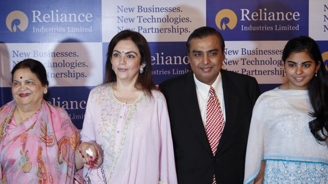 Mukesh Ambani, chairman of Reliance Industries with his mother Kokilaben Ambani (L), wife Nita Ambani (C) and daughter Isha Ambani (R) before addressing the annual shareholders meeting in Mumbai.