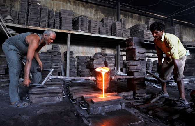 Workers lift a container filled with molten iron inside an iron casting unit at an industrial estate on the outskirts of Ahmedabad.