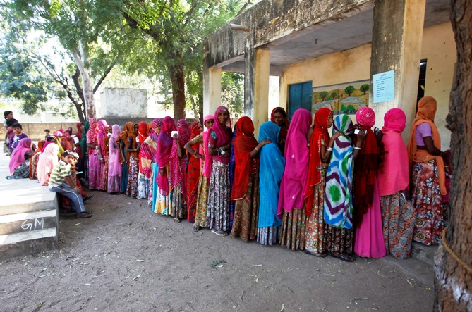 Voters line up in a queue outside a polling booth to cast their vote during the state assembly election in Maval town, located in the desert Indian state of Rajasthan, December 1, 2013.