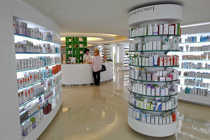 An employee talks with a customer inside a pharmacy in the Glyfada suburb of Athens, Greece.