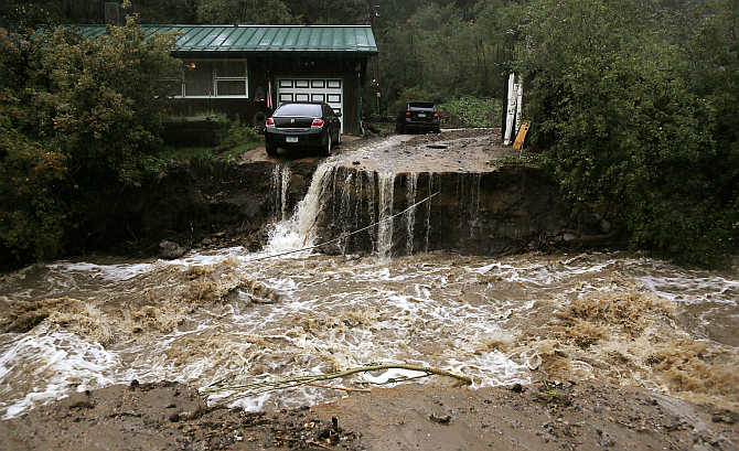 A home and car are stranded after a flash flood in Coal Creek destroyed the bridge near Golden, Colorado, United States.