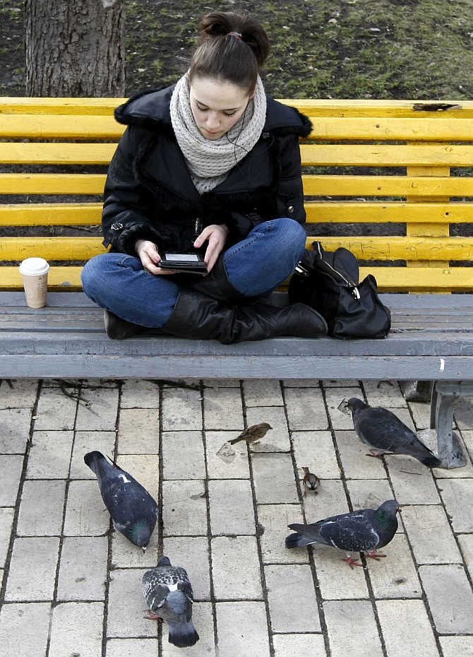 A woman sits on a bench and looks at her tablet in a park in Kiev, Ukraine.