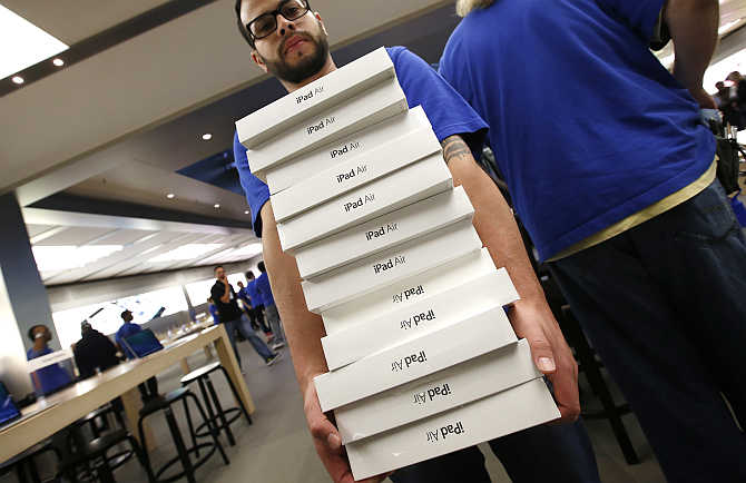 An employee carries a stack of iPad Air tablets inside the Apple Store in New York.
