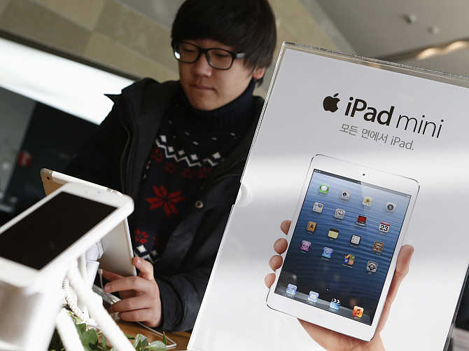 A student tries iPad mini at an electronics store in central Seoul, South Korea.