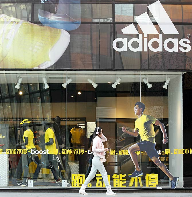 A woman walks past an Adidas shop at a shopping district in Beijing.