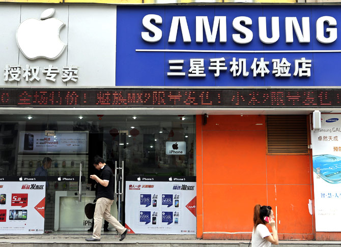 People walk past a mobile phone store selling Apple and Samsung products in Wuhan.