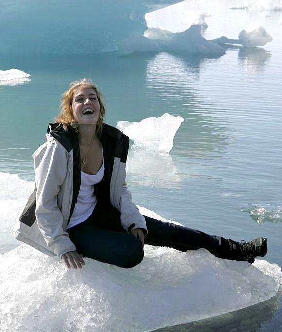 A woman poses on ice in southeast Iceland. The country has the least economic suffering.