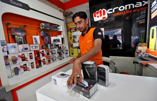 A worker displays a Micromax mobile phone inside a store in Kolkata.