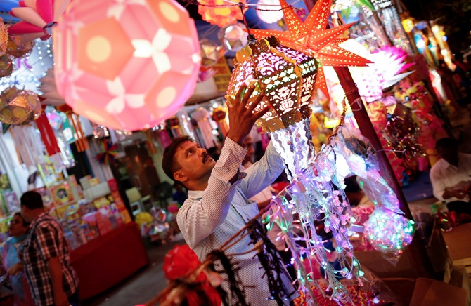 A vendor hangs a lantern for sale at a Diwali market in Mumbai.