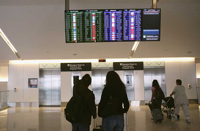 Airline passengers look at a flight status board at San Francisco International Airport in San Francisco, California.