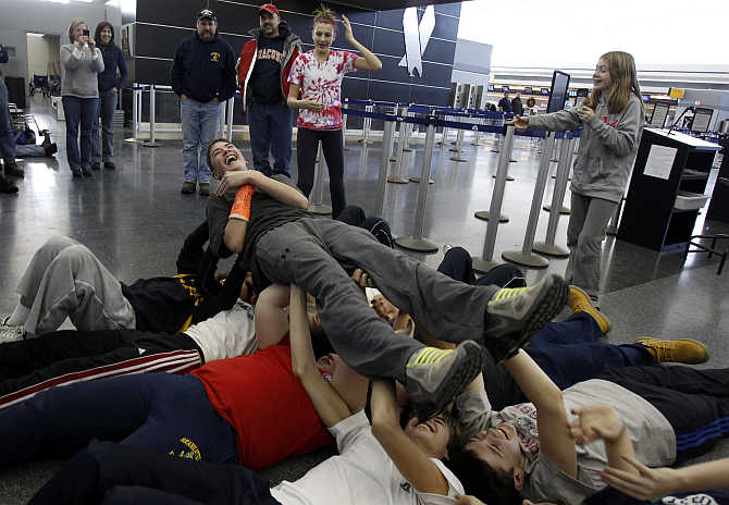 Members of the Skaneateles Bantam ice hockey team do a calisthenics drill to pass the time at JFK International Airport in New York.