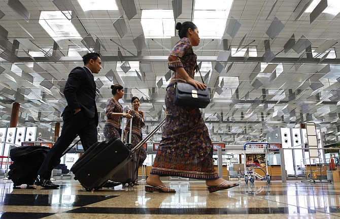 Singapore Airlines cabin crew walk past check-in counters at Terminal 3 of Singapore's Changi Airport.