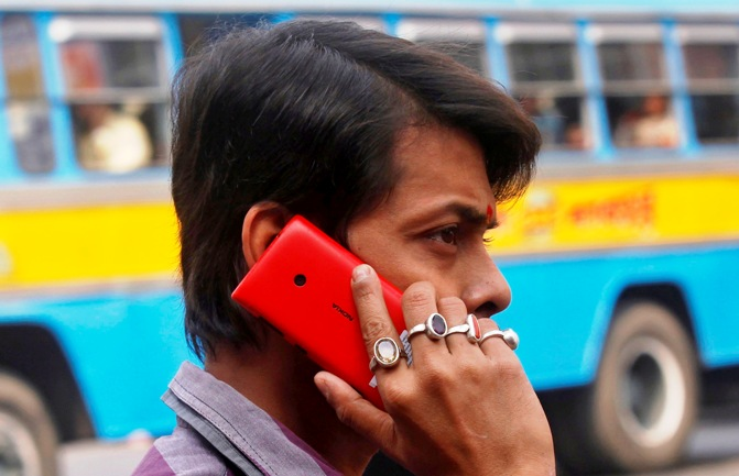 A man uses a mobile phone to make a call on a street in Kolkata.