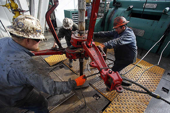 Roughnecks wrestle pipe on a True Company oil drilling rig outside Watford, North Dakota, United States.