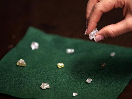 A visitor holds a 17 carat diamond at a Petra Diamonds mine in Cullinan, outside Pretoria.