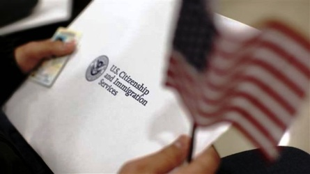 A man holds a US flag while receiving his proof of US citizenship during a ceremony in San Francisco, California
