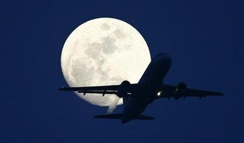 A passenger aircraft is silhouetted against the rising moon.