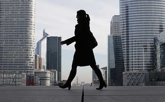 A businesswoman is silhouetted as she makes her way under the Arche de la Defense, in the financial district west of Paris, France.