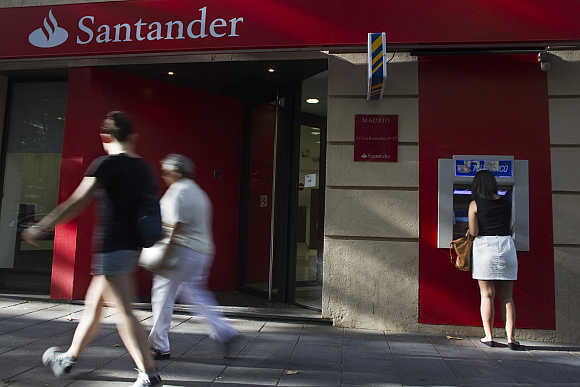 A woman uses an ATM machine at a Santander bank branch in Madrid, Spain.
