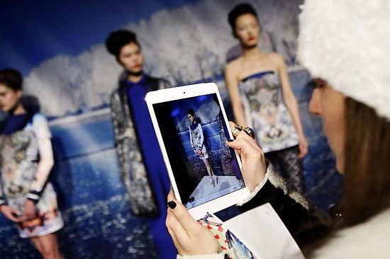 A woman takes a photo of models using an Apple iPad.