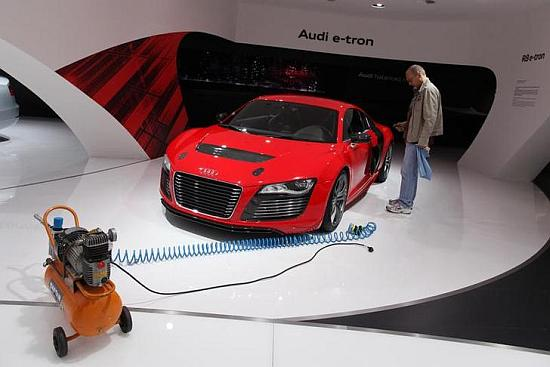 A worker for German car manufacturer Audi stands next to an R8 Audi e-tron.