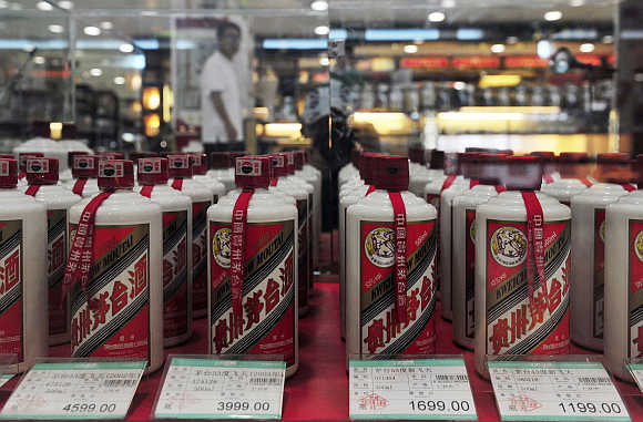 A customer walks past a glass case displaying Maotai liquors at a supermarket in Shenyang, Liaoning province.