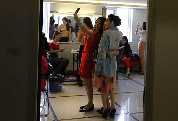 Contestants take a picture of themselves with a mobile phone backstage before the recording of a TV show in Beijing.