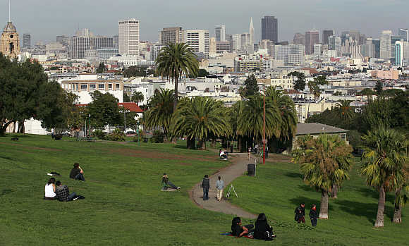 Green space of Dolores Park is shown with the skyline of San Francisco, California.