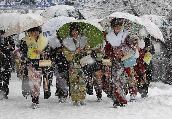 Women in kimonos walk to attend a ceremony celebrating Coming of Age Day in heavy snowfall at Toshimaen amusement park in Tokyo.