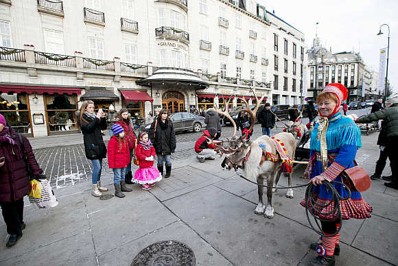A Laplander woman wearing traditional costume stands with a reindeer outside the Grand Hotel in Oslo.
