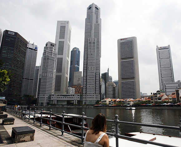 A woman looks at the skyline of Singapore's financial district.