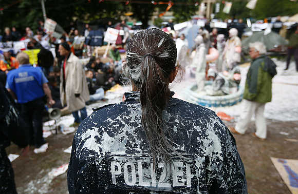 A police woman is covered with paint after being attacked by demonstrators in Frankfurt.