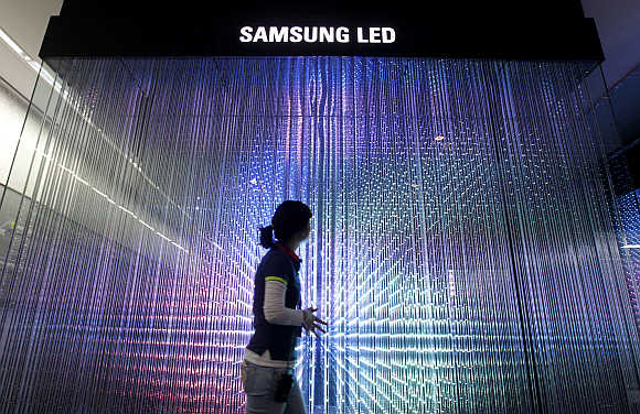 An employee of Samsung Electronics walks past LED lighting drums at a showroom in Seoul, South Korea.