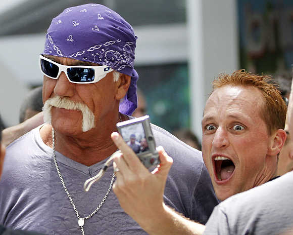 A fan takes a photo with wrestler Hulk Hogan in Los Angeles.