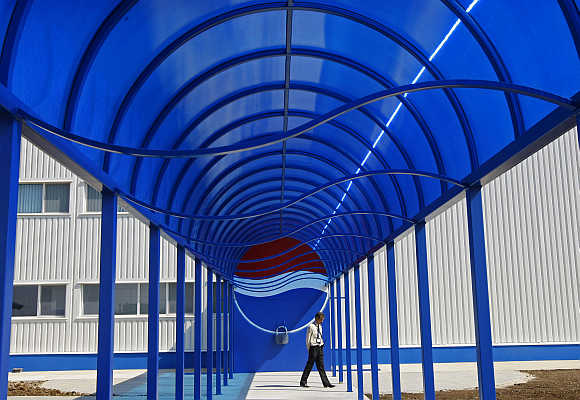 A security person walks past the entrance of the second-largest European Pepsi plant near Bucharest, Romania.