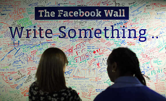 People look at the Facebook wall at their office in New York.